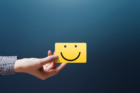 Customer Experience Concept, Happy Client Woman show a Feedback with Happy Smiley Face Card Stockfoto