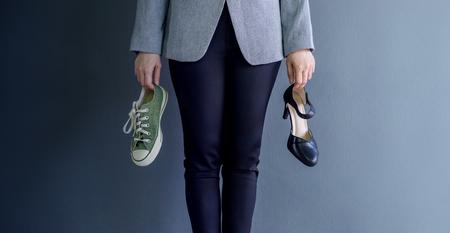 Conceito de equilíbrio de vida de trabalho, presente pela mulher de trabalho de negócios segurando uma alta cura e sapatos de tênis, Croped imagem com cópia espaço