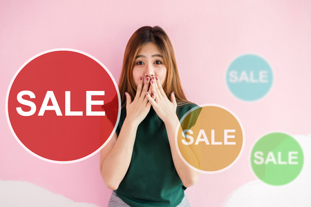 Asian Young Woman in Shocked Surprising Face when Seeing Sale Tags, Looking at camera and closed mouth with hands, Woman Lifestyle and Shopping Promotion Concept, Front view