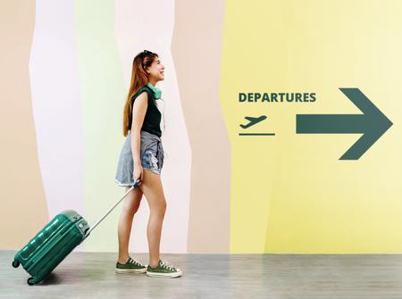 Gelukkig jonge reiziger vrouw lopen met koffer en muziek hoofdtelefoon op luchthaven, gezicht opzoeken en glimlachen, vertrek ondertekenen als achtergrond, volledige lengte, zijaanzicht