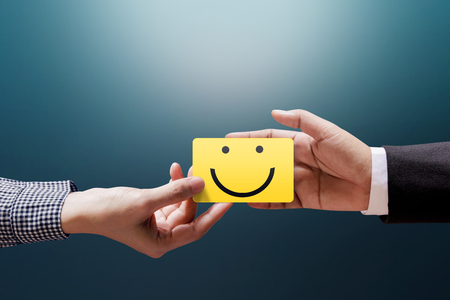 Customer Experience Concept, Happy Client Woman giving a Feedback with Happy Smiley Face Card into a Hand of Businessman