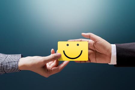 Kundenerfahrungs-Konzept, glückliche Kunden-Frau, die ein Feedback mit glücklichem Smiley Face Card in eine Hand des Geschäftsmannes gibt Standard-Bild