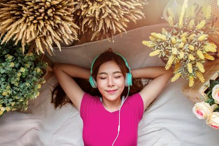 Glückliche junge Frau, die auf den Boden hörende Musik über intelligentes Telefon, geschlossene Augen und das Lächeln legt. Mädchen, das im gemütlichen Platz, umgeben durch Blume, Draufsicht sich entspannt