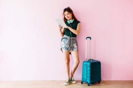 Glückliche junge Reisend-Frau mit Koffer und Musik-Kopfhörer unter Verwendung der Tablette und Lächeln, in voller Länge, Technologie auf dem Reisen, Lebensstil von modernen Leuten Standard-Bild - 92835465
