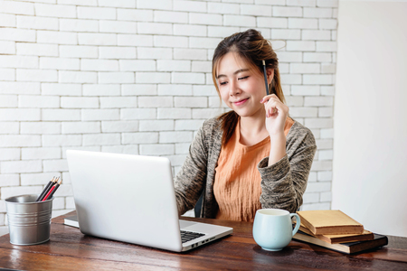 Young Woman Working on Laptop at Home Office, Work with Happy Smiley Face and Thoughtful Posture, Dressing Casual in Warm and Cozy House