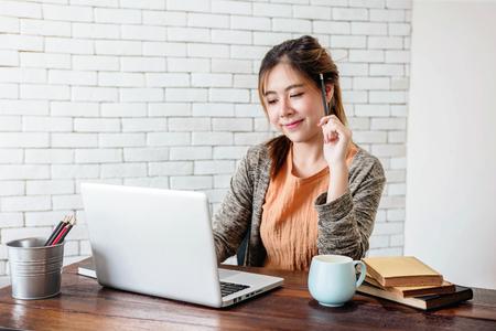 Junge Frau, die an Laptop zu Hause Büro, Arbeit mit glücklichem Smiley Face und der durchdachten Lage, zufälliges Umkleiden im warmen und gemütlichen Haus arbeitet Standard-Bild - 92835467