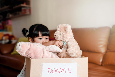Child with Donation Concept. 2 Years Old Child putting her old Dolls into a Donate Box Stockfoto