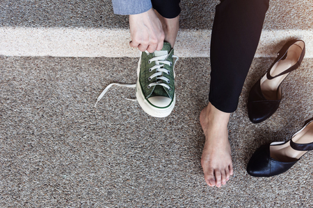 Concept de soins de santé. Femme d'affaires aux pieds nus assis dans l'escalier pour changer de chaussures du talon haut au baskets confortables. Vue de dessus