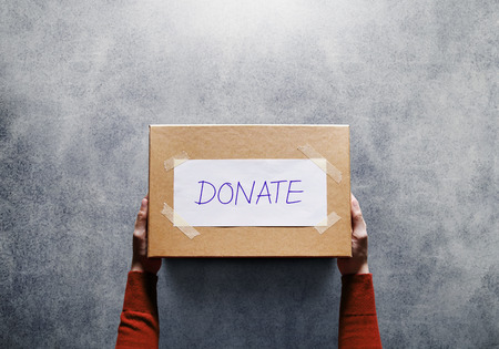 Donation Concept. Woman holding a Donate Box for Giving. Sharity activity. Top View