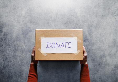 Concept de donation. Femme tenant une boîte de dons pour donner. Activité de partage. Vue de dessus