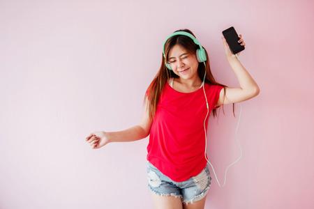 Junge Frau, die mit Musik vom intelligenten Telefon im Haus genießt, in glücklichen Moment hört und tanzt