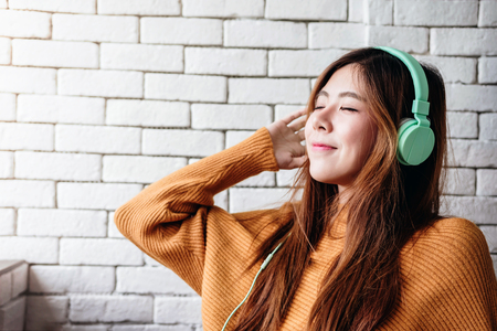 Young Woman Listening Music From Headphone in Cozy House, Closed Eyes and Relaxing in Happiness moment