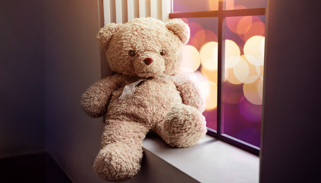Sadness and Lonelyness Concept. Lonely Teddy Bear Toy Siting Alone beside Window in the Dark Room, City Night Light as Outside View Stock Photo