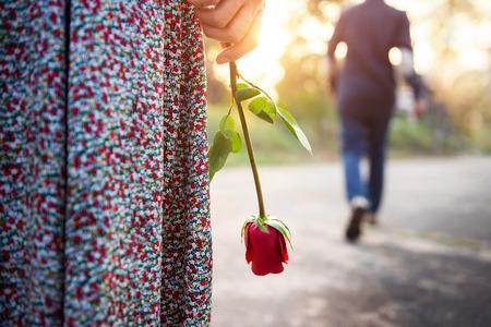 Amour de tristesse dans le concept de fin de relation, femme au c?ur brisé, debout avec une rose rouge à la main, homme flou à l'arrière, s'éloignant en arrière-plan