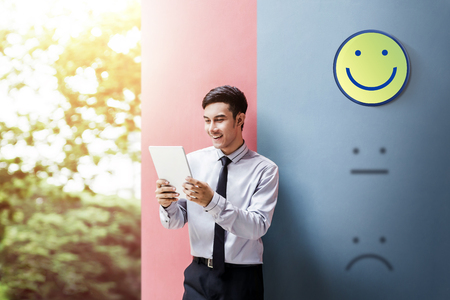Customer Experience Concept, Happy Businessman Enjoying on digital Tablet with Smiley Face Rating for a Satisfaction Survey 版權商用圖片