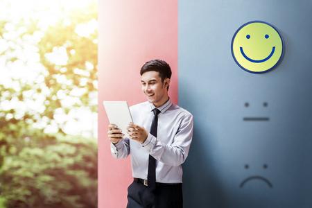 Kundenerlebnis-Konzept, glücklicher Geschäftsmann Enjoying auf digitalem Tablet mit Smiley Face Rating für eine Zufriedenheitsumfrage Standard-Bild - 94369318