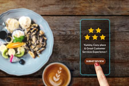 Conceito de experiência do cliente. Mulher usando Smartphone no café ou restaurante para avaliação de cinco estrelas de avaliação no aplicativo de pesquisa de satisfação on-line, revisão de alimentos, vista superior Foto de archivo