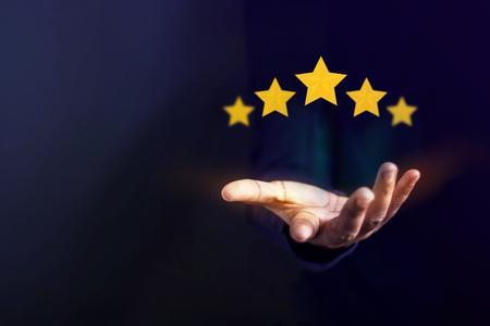 Kundenerfahrungskonzept, beste ausgezeichnete Dienstleistungen für Zufriedenheit, die durch geöffnete Hand des Kunden vorhanden sind, der eine Fünf-Sternebewertung gibt Standard-Bild