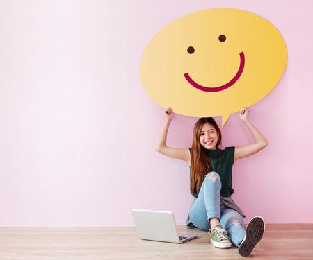 Tevreden klantconcept. Bekijk en feedback haar ervaring voor online tevredenheidsenquête. Jonge vrouw in vrolijke houding, steek de tekstballon omhoog met smileygezicht. Ga op de grond zitten met een laptop