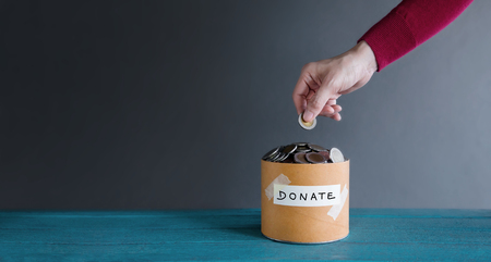 Donation Concept. Hand putting Money Coin into a Donate Box Stock Photo