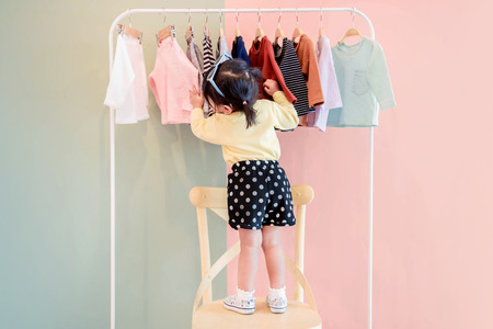 Soft Focus of a Two Years Old Child Choosing her own Dresses from Kids Cloth Rack Foto de archivo