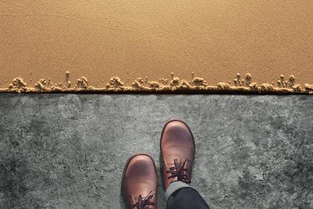 Koncepcja Comfort Zone, męski w skórzanych butach, schodzi z cementowej podłogi na piaszczystą plażę. Widok z góry Zdjęcie Seryjne