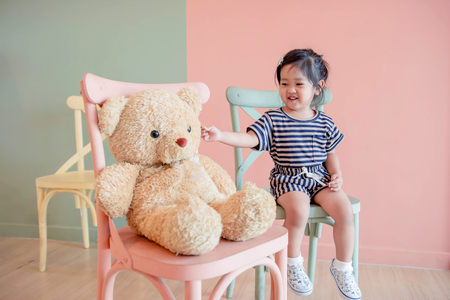 Soft Focus of a Two Years Old Child Sitting with her Teddy Bear. Happy and Lovely Kids