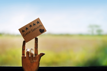 Customer Experience Concept. Happy Client leaving a Note for Review with Five Star Rating and Great Services, wooden mannequin hand with finger meaning Love