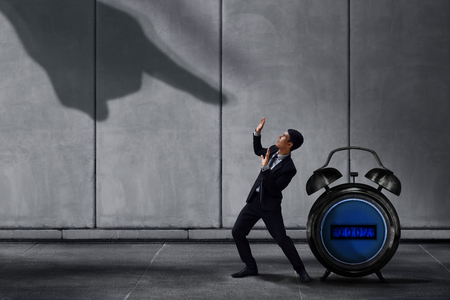 Stressed Businessman in Under Pressured Concept, Small Worker Protect an Alarm Clock with Scared posture. Shadow of Huge Pointing Hand from Terrible Boss or Customer on the Wall
