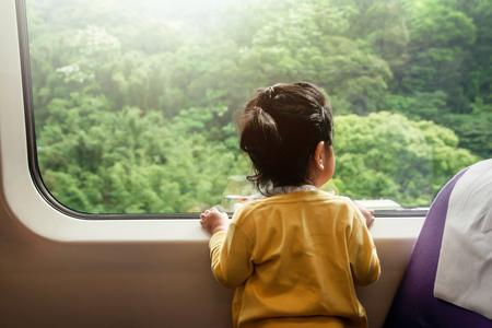 Enfants heureux et excités voyageant en train. Une fillette de deux ans à la recherche d'une large fenêtre en verre Green Forest comme vue extérieure