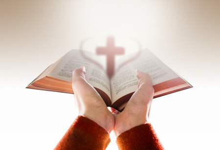 Hands of Woman Raise up a Bible for Praying with Blurred Shape of Cross and Heart 스톡 콘텐츠