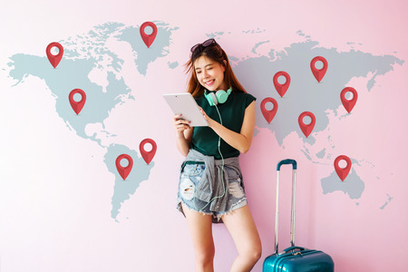 Happy Young Traveler Woman standing with Suitcase and using Tablet to Finding her Destination for Next Trip. Technology on Traveling Concept. World Map with Mark Icon on the Wall Foto de archivo