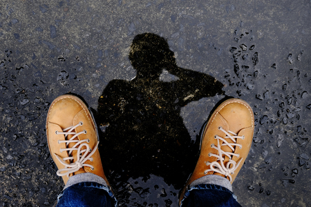 Top View of Photogrpaher taking Self Portrait by Reflection Shadow on the Ground after stopped Raining Foto de archivo