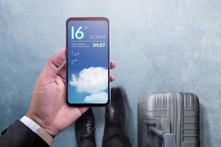 Mobiele technologie voor reizend concept. Bovenaanzicht van zakenman wandelen met koffer, smartphone houden om weersinformatie op de luchthaven te controleren
