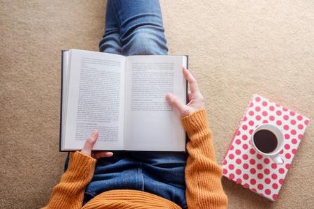 Concepto de lectura. Enfoque suave de mujer joven relajante por libro y café en casa acogedora, sentarse en el suelo, vista superior