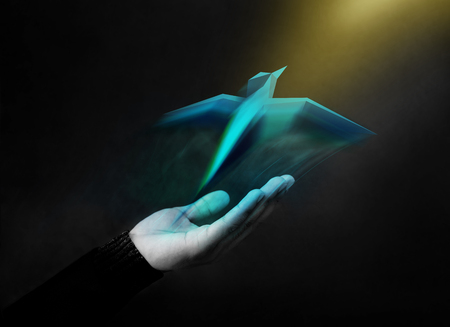 Freedom Concept. Digital Geometric Bird Soaring Up from an Opened Hand into the Golden Light Stock Photo