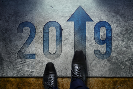 2019 Year Concept. Top View of Male with Formal Oxford Shoes standing on the Floor to Steps into number and Forward Arrow