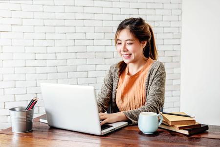 Glückliche junge Freelancer-Frau, die in einem gemütlichen Haus am Computer-Laptop arbeitet, moderner Lebensstil von Menschen der neuen Generation Standard-Bild