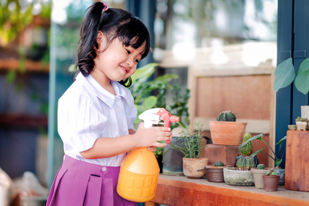 Happy Cute Asian Girl Enjoying with Gardening Activities, A Three Years old Child in Student Uniform is Watering Plant in the Garden, Happiness Moment Stock fotó