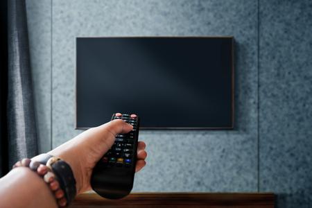 Viendo el concepto de televisión. Mano sujetando el control remoto del televisor para controlar o cambiar de canal. Relajación en la sala de estar moderna. Centrarse en el control remoto Foto de archivo