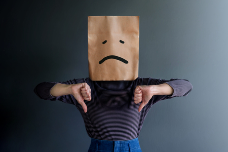 Customer Experience or Human Emotional Concept. Woman Covered her Face by Paper Bag and present Sadness Feeling and Disappointed by Drawn Line Cartoon and Body Language Foto de archivo - 119596134