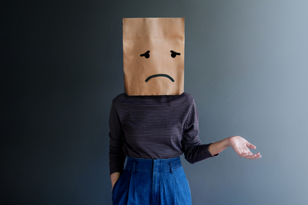 Customer Experience or Human Emotional Concept. Woman Covered her Face by Paper Bag and present Sadness Feeling and Disappointed by Drawn Line Cartoon and Body Language Foto de archivo - 119596292