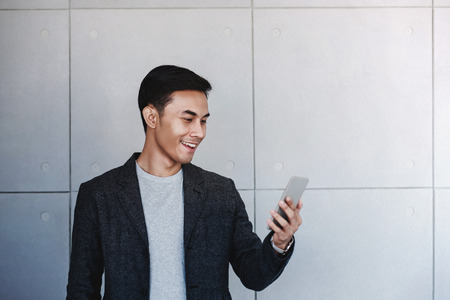 Portrait of Young Happy Businessman Using Smartphone. Standing by the Industrial Concrete Wall. Reading Message via Mobile Phone and Smiling Stock fotó