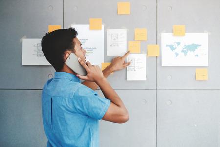 Jeune homme d'affaires asiatique travaillant dans la salle de réunion du bureau et parlant via Smartphone. Homme analysant les plans de données et le projet. Concentrez-vous sur la note de document à bord Banque d'images
