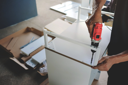 Assembling Furniture at Home. Moving for a New House or DIY Concept. Craftsman using Cordless Screwdriver to Installing the Cabinet.