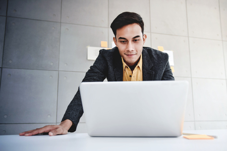 Happy Young Asian Businessman Working on Computer Laptop in Office