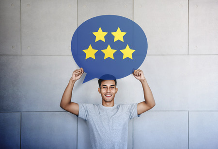 Customer Experience Concept. Young Man with Happy Face Showing Five Star Services Rating Satisfaction on Speech Bubble Card. Happy Clients Feedback and Online Review