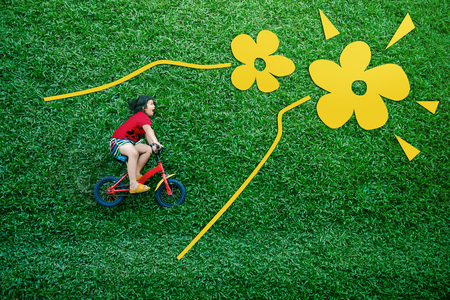 Rear View of a Happy Asian Kids. Girl on Bicycle Lay Down at Green lawn in Spring or Summer Day. Excited Asian Children in her Outdoor Activity
