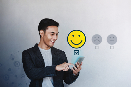 Customer Experience Concept. Young Businessman Giving his Positive Review in Satisfaction Online Survey. Happy Client Submit a Smiling Face for Excellent Services via Smartphone Banco de Imagens