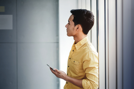Young Businessman Standing by the Window in Office. Holding Smartphone and looking at the Wall